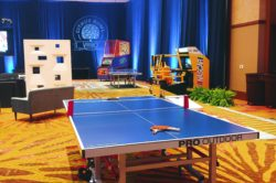 Table Tennis rental for corporate event with a daytona USA arcade game in the background